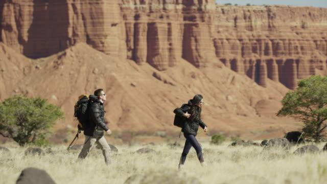 vídeos de stock, filmes e b-roll de wide panning shot of couple hiking in desert / torrey, utah, united states - câmera seguindo movimento