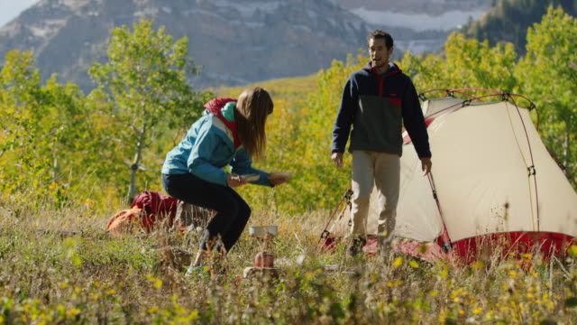 wide panning shot of couple kissing with food cooked on camping stove / american fork canyon, utah, united states - american fork canyon bildbanksvideor och videomaterial från bakom kulisserna