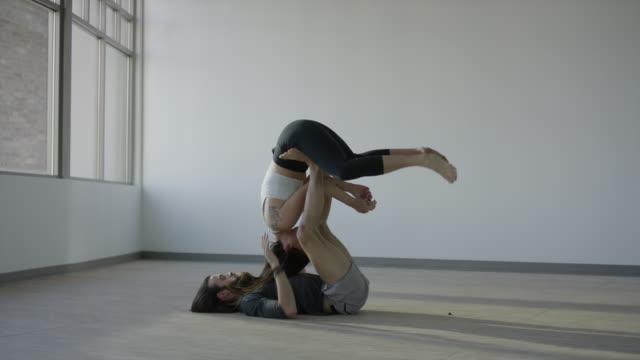 stockvideo's en b-roll-footage met wide panning shot of couple practicing acro yoga in studio / orem, utah, united states - orem utah