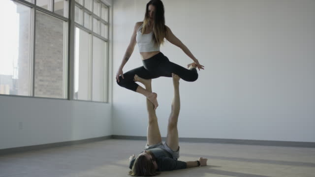 Wide panning shot of couple practicing acro yoga in studio / Orem, Utah, United States