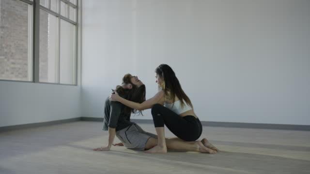 wide panning shot of couple practicing acro yoga in studio / orem, utah, united states - orem utah stock videos & royalty-free footage