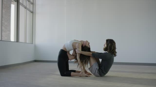 vídeos de stock, filmes e b-roll de wide panning shot of couple practicing acro yoga in studio / orem, utah, united states - orem utah