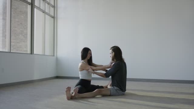 wide panning shot of couple practicing acro yoga in studio / orem, utah, united states - legs apart stock videos and b-roll footage