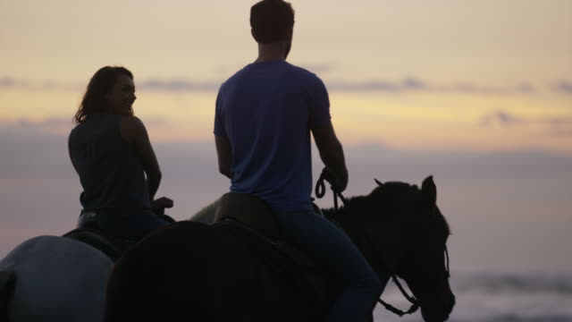 vídeos de stock, filmes e b-roll de wide panning shot of couple riding horseback on beach at sunset / esterillos, puntarenas, costa rica - montar um animal