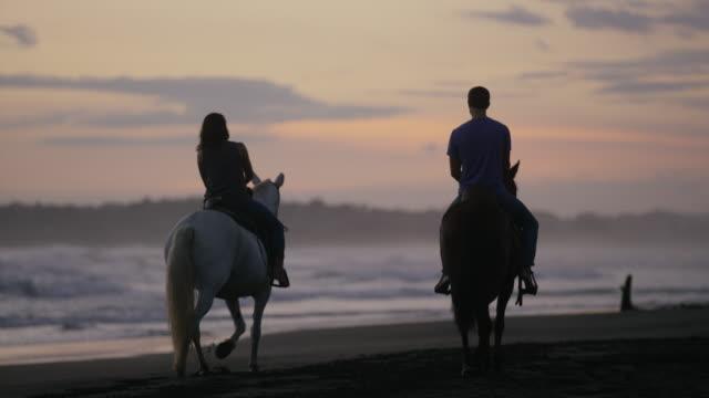 Wide panning shot of couple riding horseback on beach at sunset / Esterillos, Puntarenas, Costa Rica