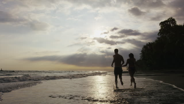 wide panning shot of couple running on beach at sunset / esterillos, puntarenas, costa rica - 避ける点の映像素材/bロール