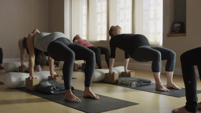 wide panning shot of expectant mothers and instructor in yoga class / provo, utah, united states - provo stock videos & royalty-free footage