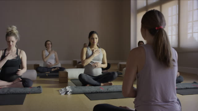 Wide panning shot of expectant mothers and instructor in yoga class / Provo, Utah, United States