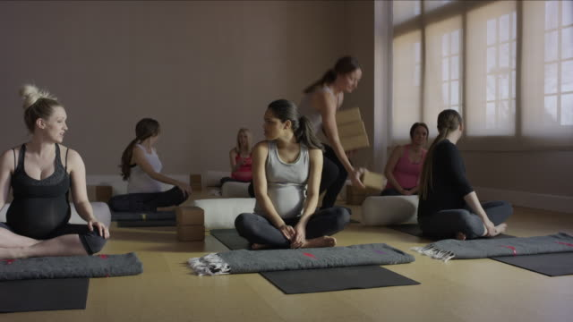 wide panning shot of expectant mothers waiting in yoga class / provo, utah, united states - provo stock videos & royalty-free footage