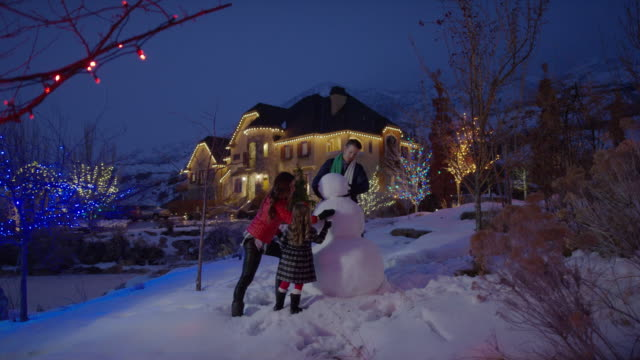wide panning shot of family building snowman / cedar hills, utah, united states - making a snowman stock videos & royalty-free footage