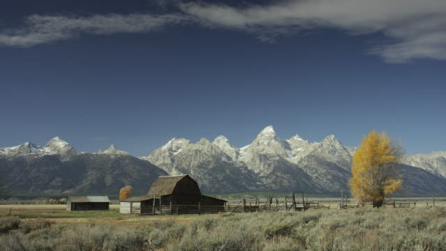 Wide panning shot of farm and mountains in remote landscape / Wyoming, United States
