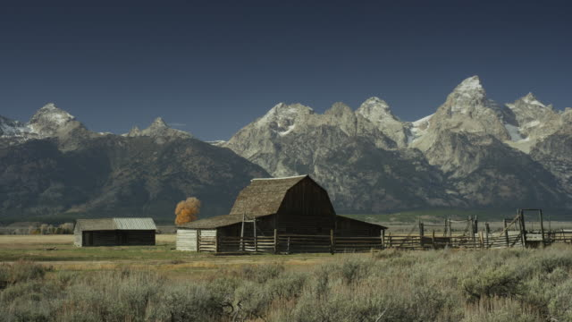 wide panning shot of farm and mountains in remote landscape / wyoming, united states - グランドティトン国立公園点の映像素材/bロール
