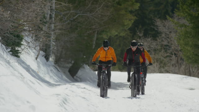 wide panning shot of friends riding fat bikes on mountain / american fork canyon, utah, united states - american fork canyon bildbanksvideor och videomaterial från bakom kulisserna