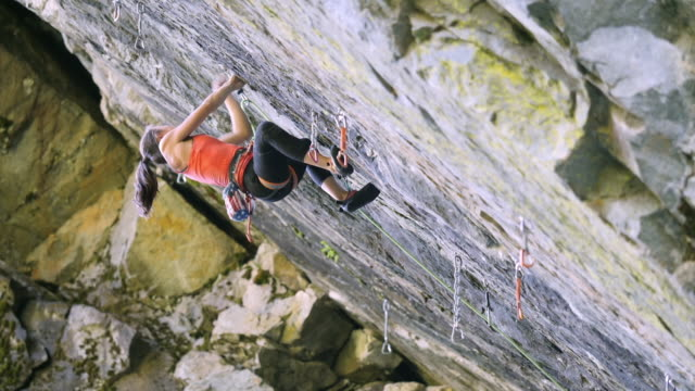 wide panning shot of girl climbing rock and falling - steep stock videos & royalty-free footage