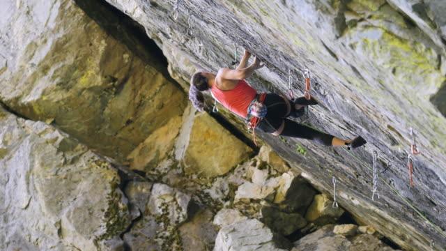 Wide panning shot of girl climbing rock