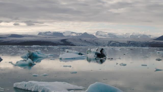 Wide panning shot of glaciers floating in lagoon / Jokulsarlon, Iceland