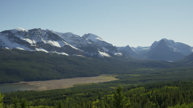 wide panning shot of green valley and mountains / glacier national park, montana, united states - wide stock videos and b-roll footage