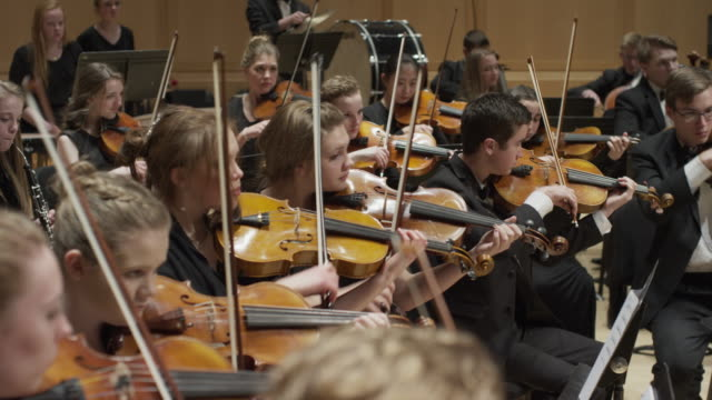wide panning shot of high school orchestra performing on stage / salt lake city, utah, united states - orchestra stock videos & royalty-free footage
