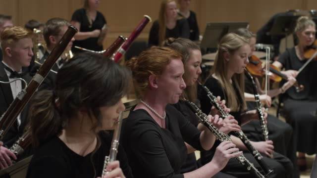wide panning shot of high school orchestra performing on stage / salt lake city, utah, united states - woodwind instrument stock videos and b-roll footage
