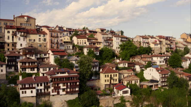 Wide panning shot of houses on hillside / Veliko Tarnovo, Bulgaria