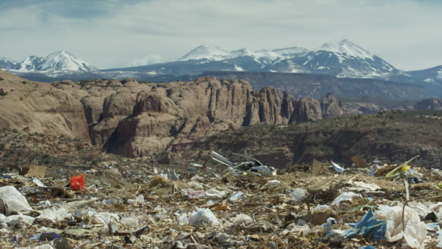 Wide panning shot of landfill garbage in mountain range landscape / Moab, Utah, United States