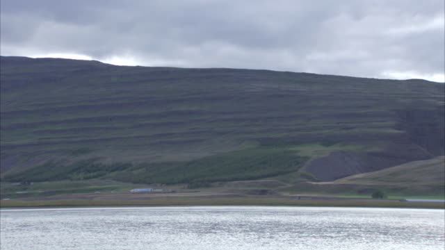 wide panning shot of loch and hills surrounding it - loch点の映像素材/bロール