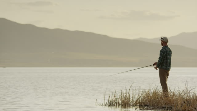 Wide panning shot of man fly fishing at lake / Vineyard, Utah, United States