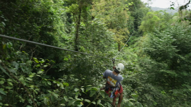wide panning shot of man playing on zipline in rain forest / quepos, puntarenas, costa rica - ロープスライダー点の映像素材/bロール