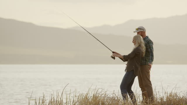 wide panning shot of man watching woman fly fishing at lake / vineyard, utah, united states - fly fishing stock videos and b-roll footage