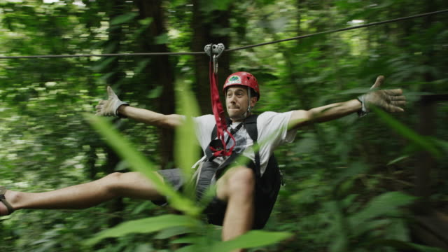 wide panning shot of man ziplining in rain forest / quepos, puntarenas, costa rica - costa rica stock videos & royalty-free footage