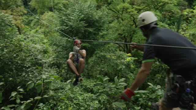 wide panning shot of man ziplining in rain forest / quepos, puntarenas, costa rica - ロープスライダー点の映像素材/bロール