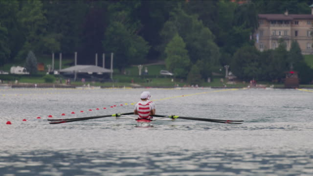 wide panning shot of men rowing on lake / lake bled, slovenia - lago di bled video stock e b–roll
