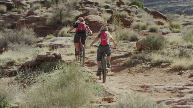 Wide panning shot of mother and daughter riding mountain bikes in desert / Moab, Utah, United States