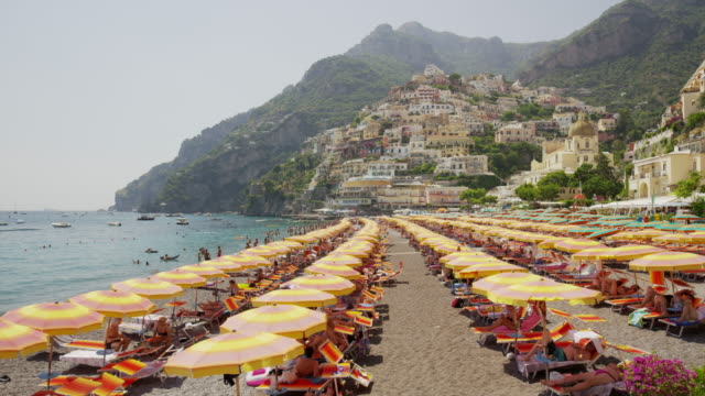 Wide panning shot of people at urban waterfront beach / Positano, Campania, Italy