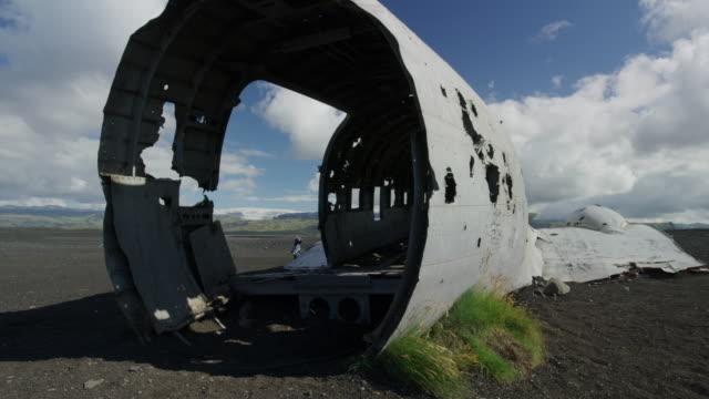 Wide panning shot of people exploring airplane wreckage / Vestur-Skaftafellssysla, Iceland