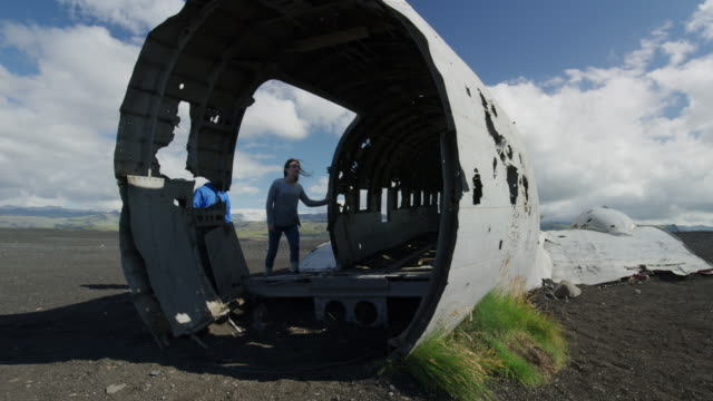 wide panning shot of people exploring airplane wreckage / vestur-skaftafellssysla, iceland - wrack stock-videos und b-roll-filmmaterial