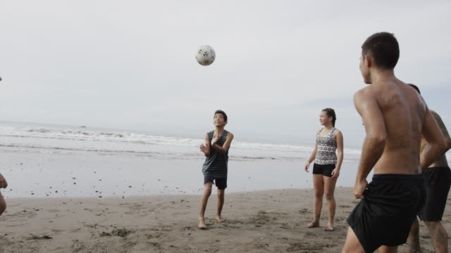 wide panning shot of people playing with soccer ball on beach / esterillos, puntarenas, costa rica - barefoot stock videos & royalty-free footage
