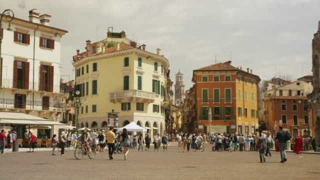 wide panning shot of people walking in town square near ruins / verona, italy - piazza video stock e b–roll