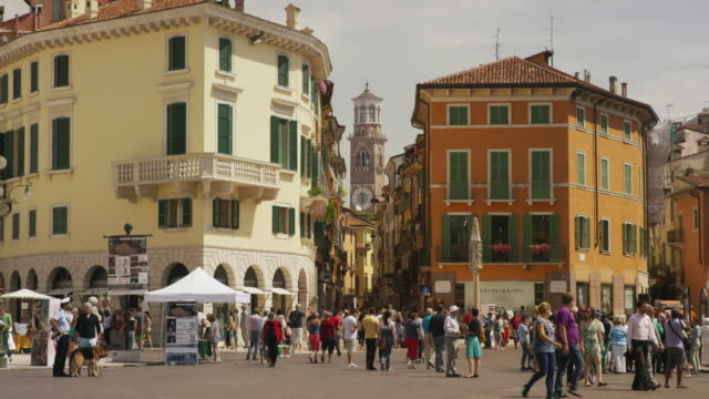 Wide panning shot of people walking in town square / Verona, Italy