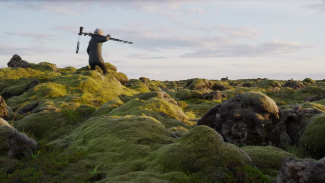 Wide panning shot of photographer arranging tripod mossy landscape / Iceland