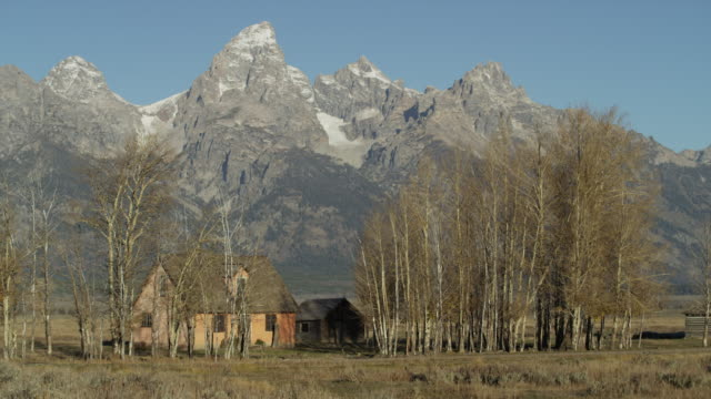 wide panning shot of remote house and mountains / wyoming, united states - jackson hole stock-videos und b-roll-filmmaterial