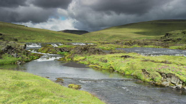 wide panning shot of river flowing through rolling landscape / iceland - rolling landscape stock videos & royalty-free footage