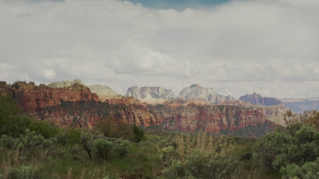 Wide panning shot of scenic view of clouds over canyon / Zion National Park, Utah, United States