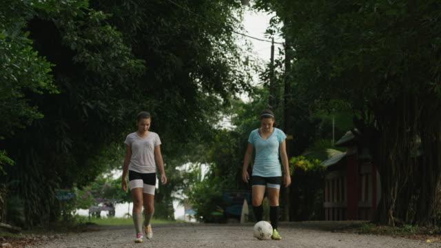 wide panning shot of soccer players kicking ball on dirt road / esterillos, puntarenas, costa rica - puntarenas stock-videos und b-roll-filmmaterial
