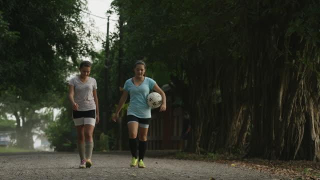 wide panning shot of soccer players walking on dirt road / esterillos, puntarenas, costa rica - puntarenas stock-videos und b-roll-filmmaterial
