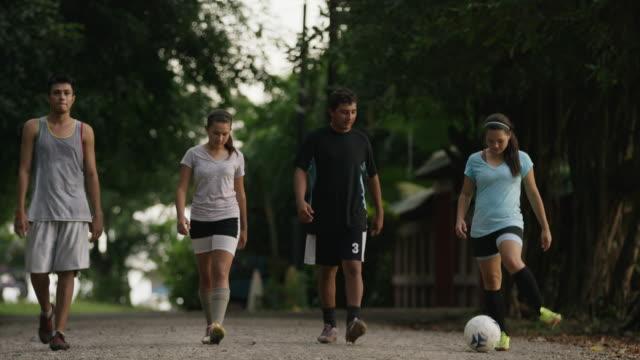 Wide panning shot of soccer team walking on dirt road / Esterillos, Puntarenas, Costa Rica