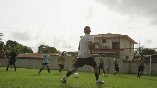 wide panning shot of soccer teams playing on field / esterillos, puntarenas, costa rica - puntarenas stock-videos und b-roll-filmmaterial