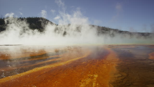Wide panning shot of steam rising from Grand Prismatic spring / Yellowstone National Park, Wyoming, United States