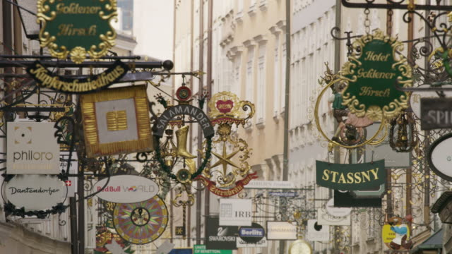 Wide panning shot of store signs in city / Salzburg, Austria