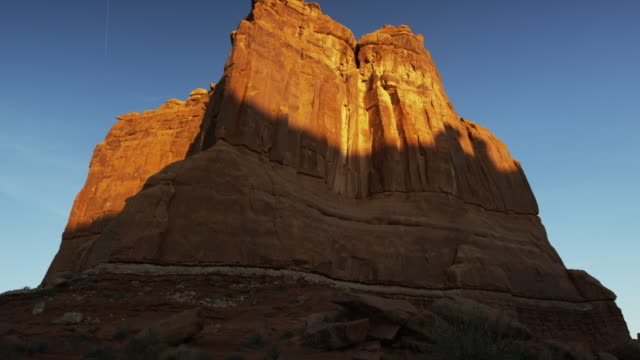 Wide panning shot of tall rock formation in national park / Arches National Park, Utah, United States
